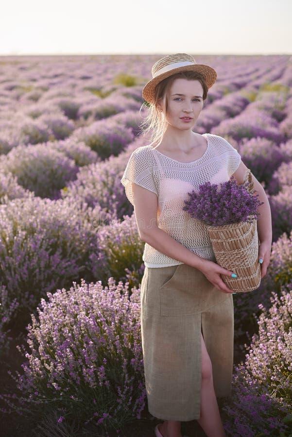 有柳条筐的卖花人用淡紫色在她的手上寻找在领域的最佳的鲜花 库存照片