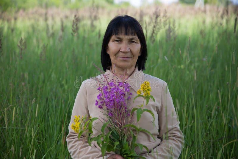 有柳草的资深深色的妇女在领域 免版税图库摄影