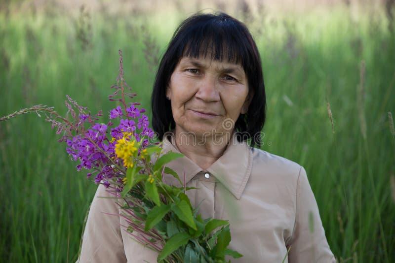 有柳草的资深深色的妇女在领域 库存照片