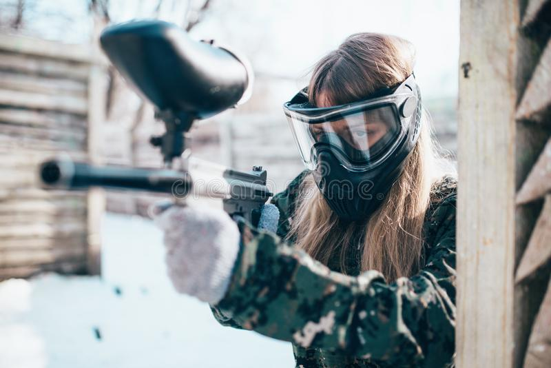 有标志枪的女性迷彩漆弹运动球员在手上 免版税库存图片