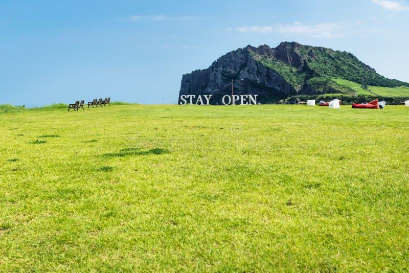 有标志`逗留开放`和木椅子的有Ilchulbong的在背景中, Seongsan,济州海岛草甸和装豆子小布袋 库存图片