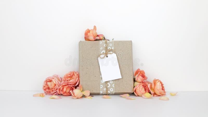 有标记大模型的礼物盒,橙色花 库存图片