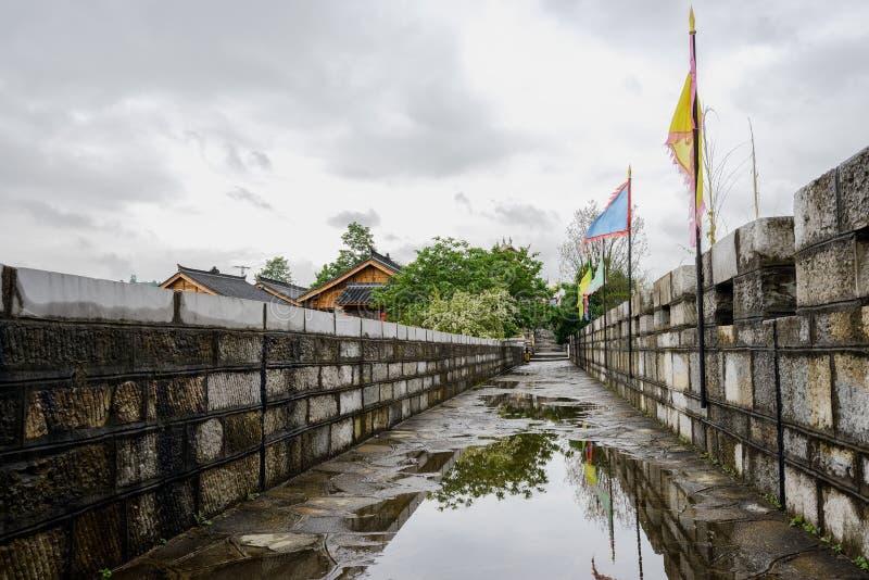 有栏杆和城垛的湿石墙在阴沉的春天af 免版税库存照片