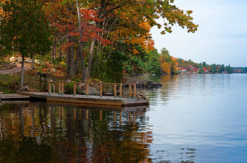有栏杆的木船坞在秋天场面 图库摄影