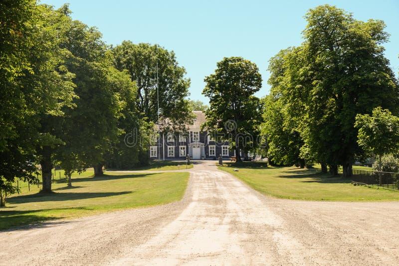 有树的庄园住宅在前面 免版税库存照片