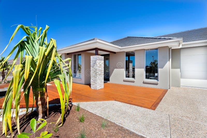 有树的现代房子和与木和石ya的车库 免版税图库摄影