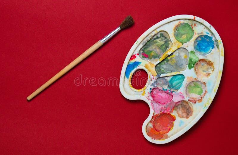 有树胶水彩画颜料油漆的塑料在红色纸背景的调色板和刷子 顶视图 免版税库存图片