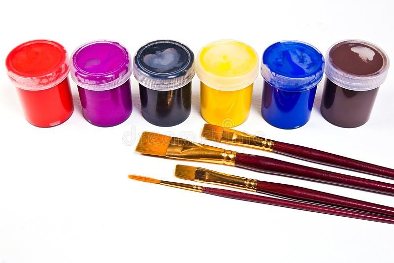 有树胶水彩画颜料油漆和不同的种类的瓶a的刷子 免版税库存照片