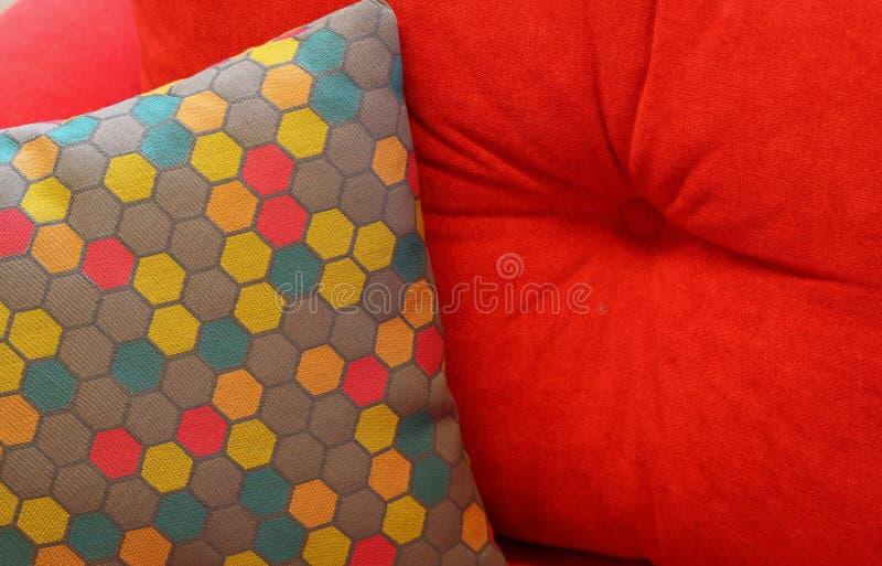 有样式的色的枕头在红色沙发 休息,睡觉,舒适概念 免版税库存照片