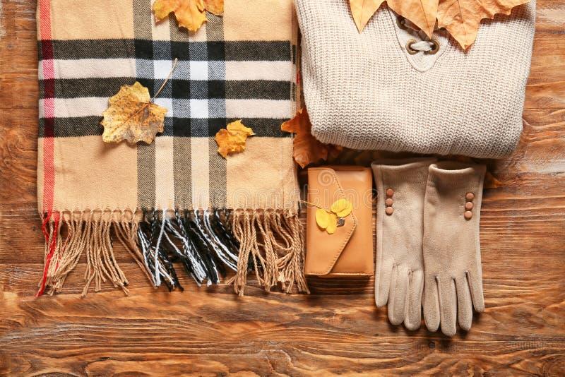 有格子花呢披肩、辅助部件和秋叶的时髦的成套装备在木背景,顶视图 免版税库存图片