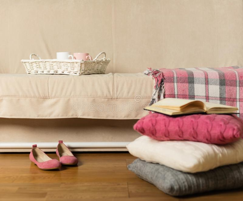 有格子花呢披肩和五颜六色的枕头的桃红色,灰色,白色a米黄沙发 库存照片