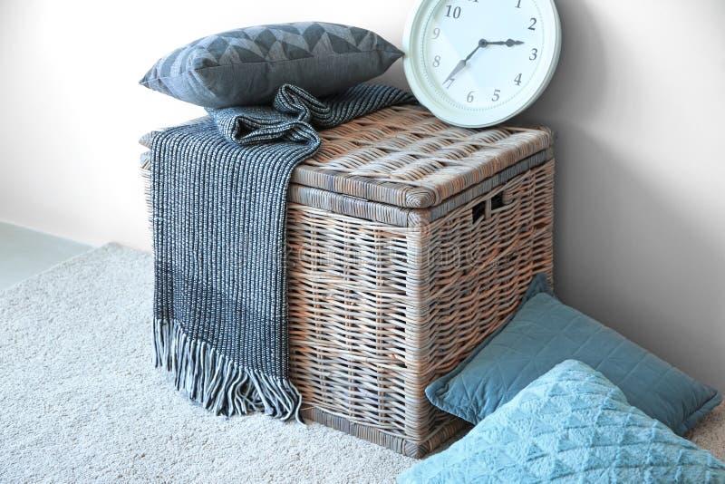 有格子花呢披肩和时钟的软的枕头在户内轻的墙壁附近的柳条筐 免版税库存照片