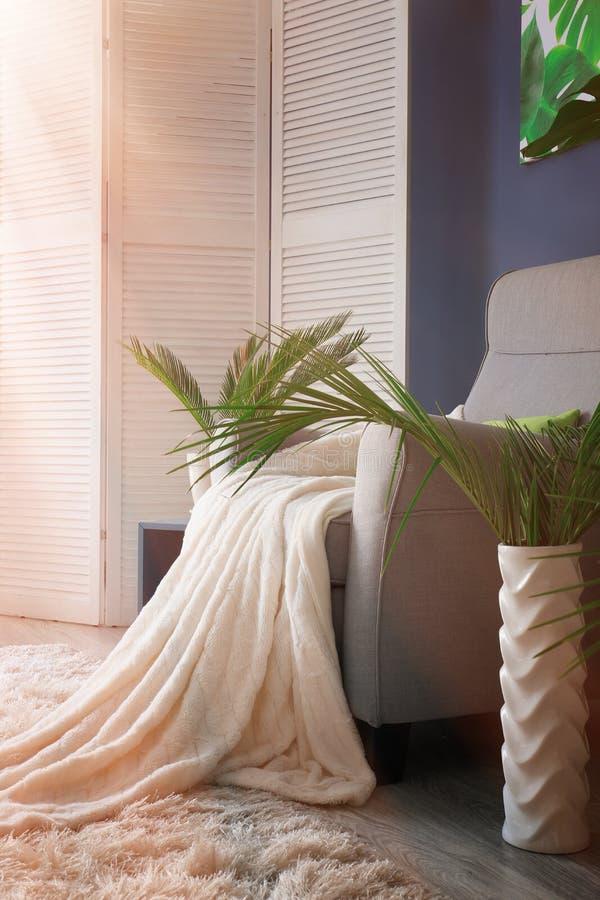 有格子花呢披肩和热带叶子的舒适的扶手椅子在屋子里 免版税库存图片