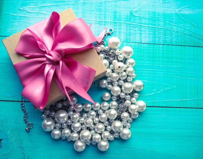 有桃红色丝带弓的礼物盒和在蓝色木桌上的珍珠首饰 库存照片