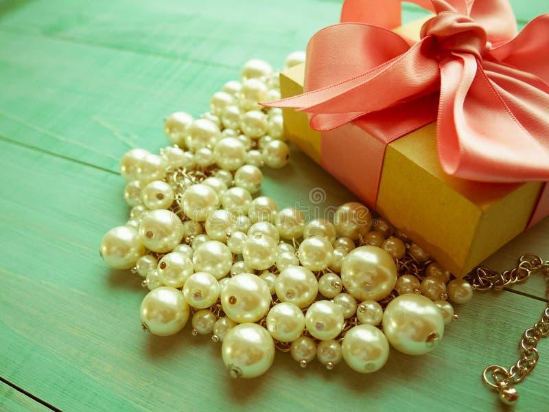 有桃红色丝带弓的礼物盒和在蓝色木桌上的珍珠首饰 免版税库存图片