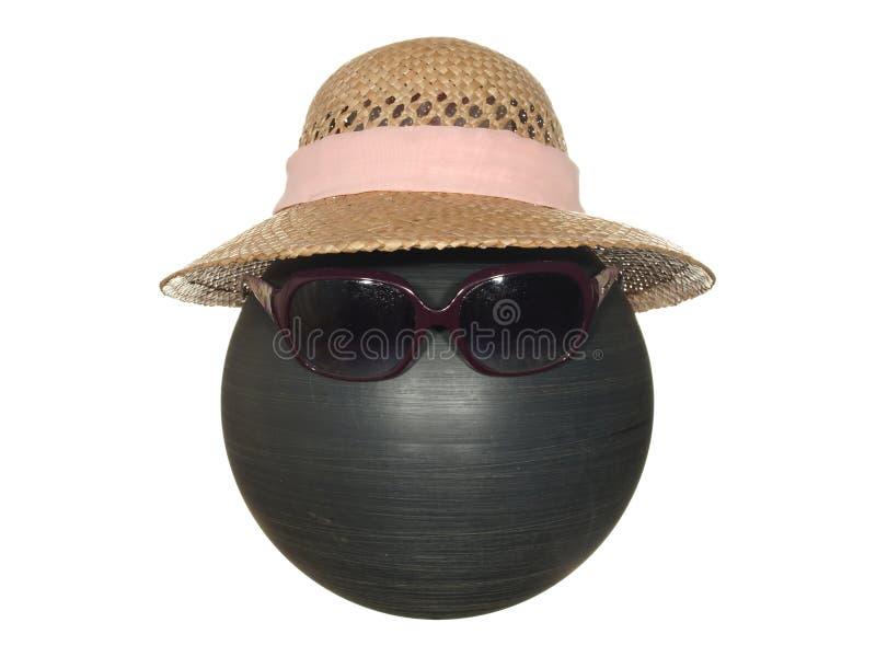 有桃红色丝带的夫人的草帽和在白色背景隔绝的一个黑塑料球的黑暗的安全玻璃 免版税库存图片