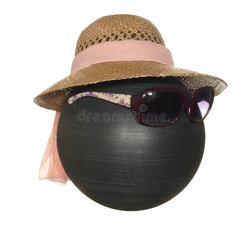 有桃红色丝带的夫人的草帽和在白色背景隔绝的一个黑塑料球的黑暗的安全玻璃 库存图片