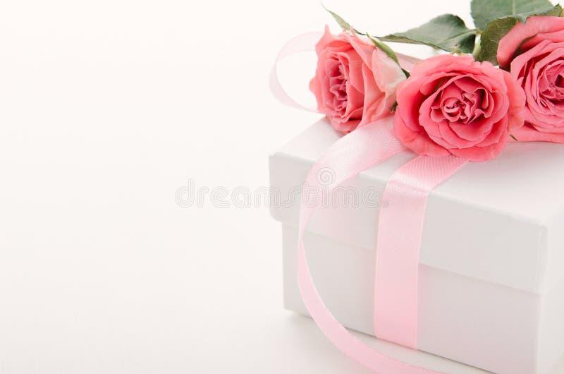 有桃红色丝带的白色在白色背景的礼物盒和玫瑰 一件礼物为情人节,生日,妇女的天 复制 库存图片