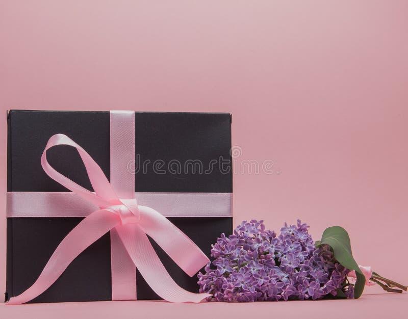 有桃红色丝带的礼物盒在桃红色背景,装饰用丁香 日母亲s 生日华伦泰` s天 复制空间 免版税库存照片