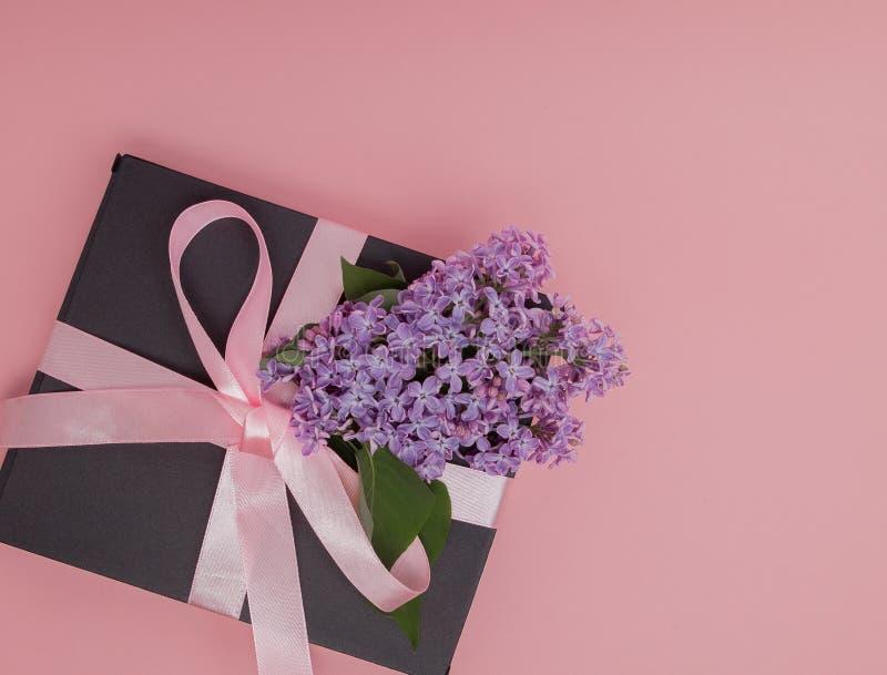 有桃红色丝带的礼物盒在桃红色背景,装饰用丁香 日母亲s 生日华伦泰` s天 复制空间 库存照片