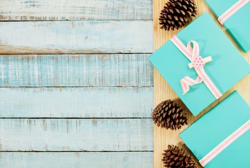 有桃红色丝带的蓝色在木头的礼物盒和fircones 库存照片