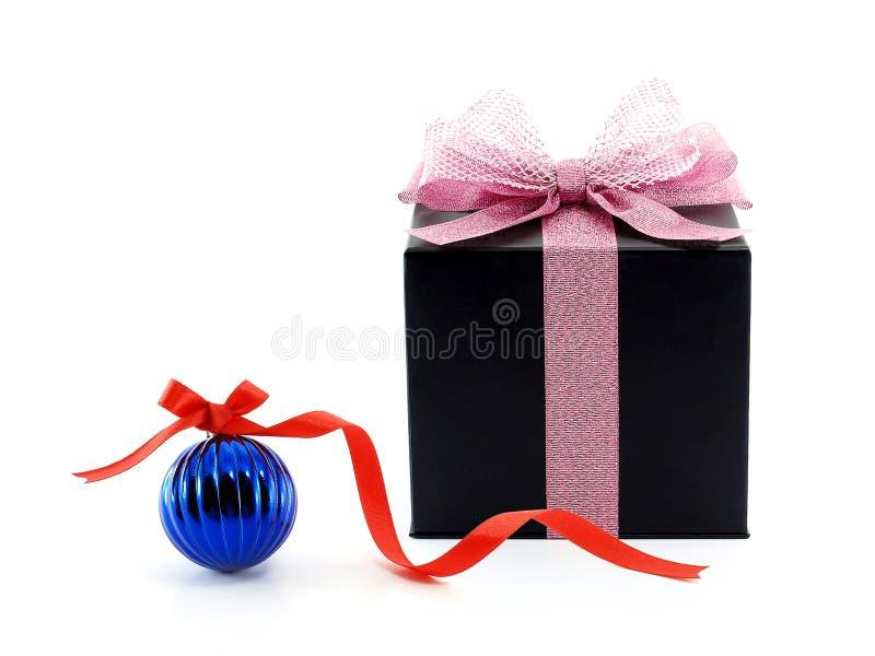 有桃红色丝带网弓的黑礼物盒和与在白色背景隔绝的红色丝带弓的蓝色光滑的圣诞节球 免版税库存照片
