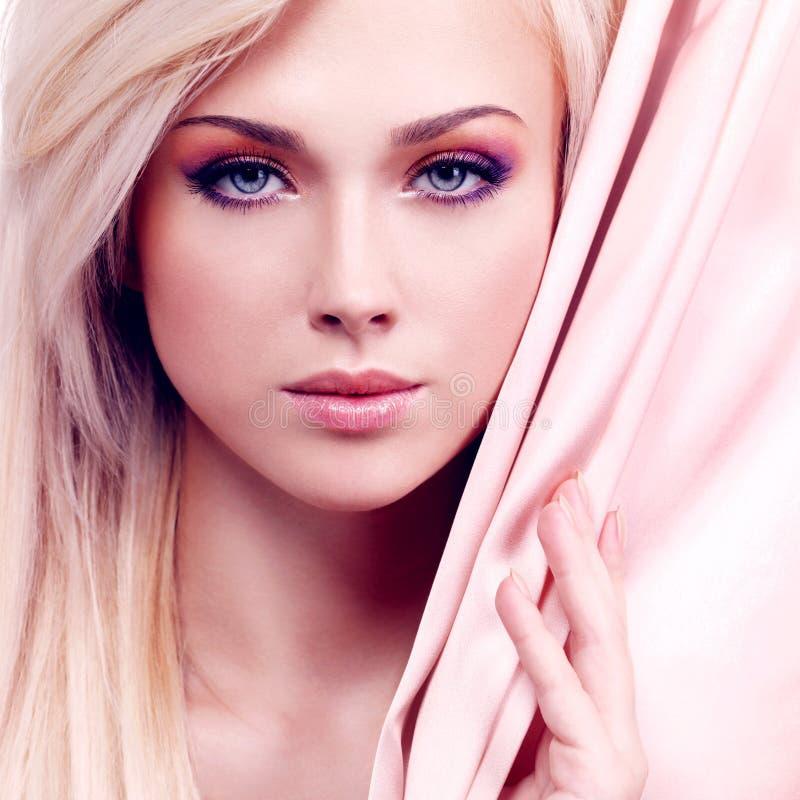 有桃红色丝绸的性感的嫩妇女。 库存照片