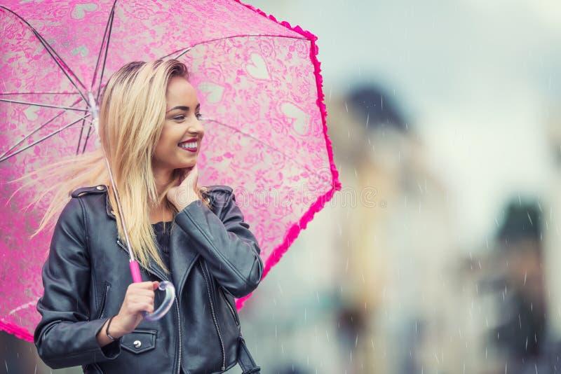 有桃红色伞的可爱的少妇在雨和强风 有伞的女孩在秋天天气 库存照片