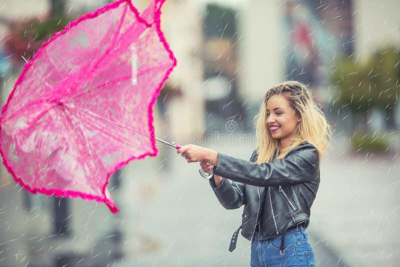 有桃红色伞的可爱的少妇在雨和强风 有伞的女孩在秋天天气 免版税库存照片