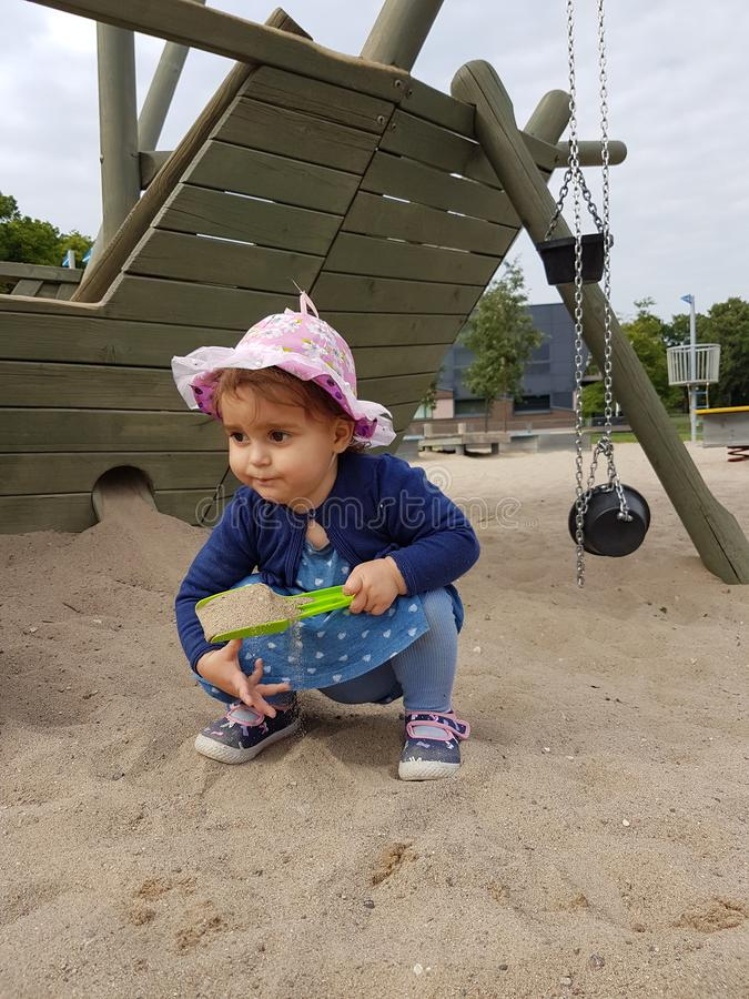 有桃红色使用在沙子的帽子和蓝色礼服的逗人喜爱的小孩 免版税图库摄影
