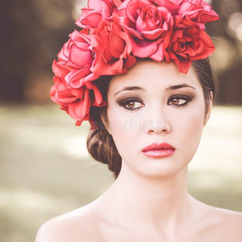 有桃红色和红色花的年轻美丽的日本妇女 免版税库存照片