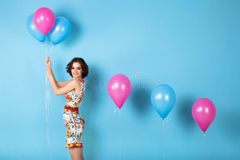 有桃红色和蓝色气球的愉快的少妇 库存图片