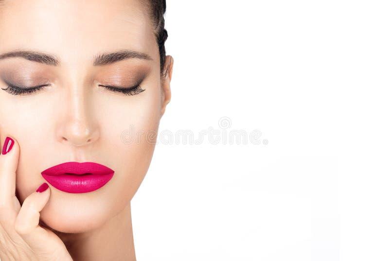 有桃红色嘴唇和钉子的美丽的年轻时尚妇女 秀丽和构成概念 在白色隔绝的特写镜头面孔 免版税库存图片