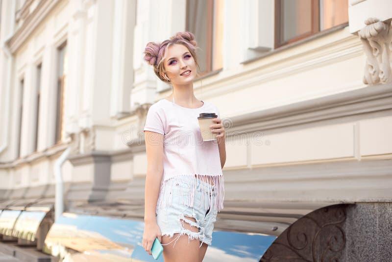 有桃红色头发发型的微笑的美女步行沿着向下有享用一美丽晴朗的一杯咖啡的街道 库存图片
