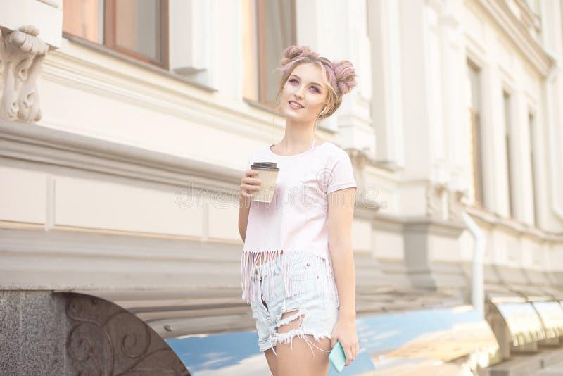 有桃红色头发发型的微笑的美女步行沿着向下有享用一美丽晴朗的一杯咖啡的街道 免版税库存照片