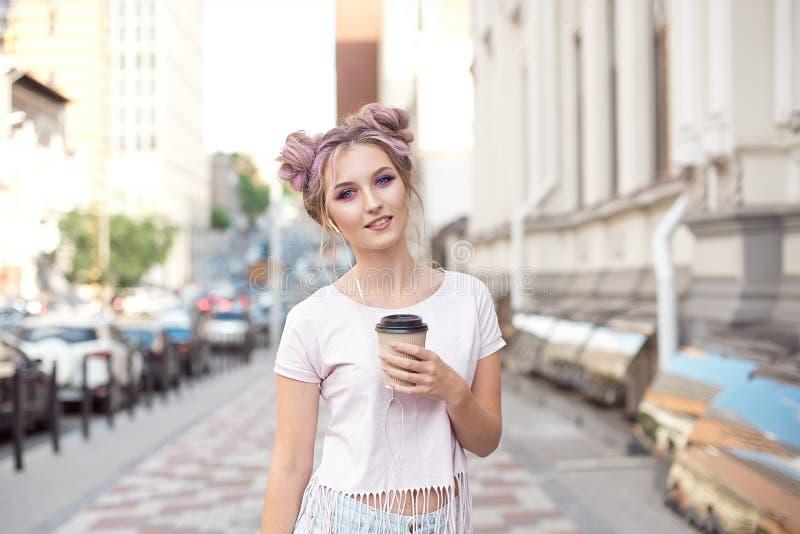 有桃红色头发发型的微笑的美女步行沿着向下有享用a的一杯纸板咖啡的街道 库存图片