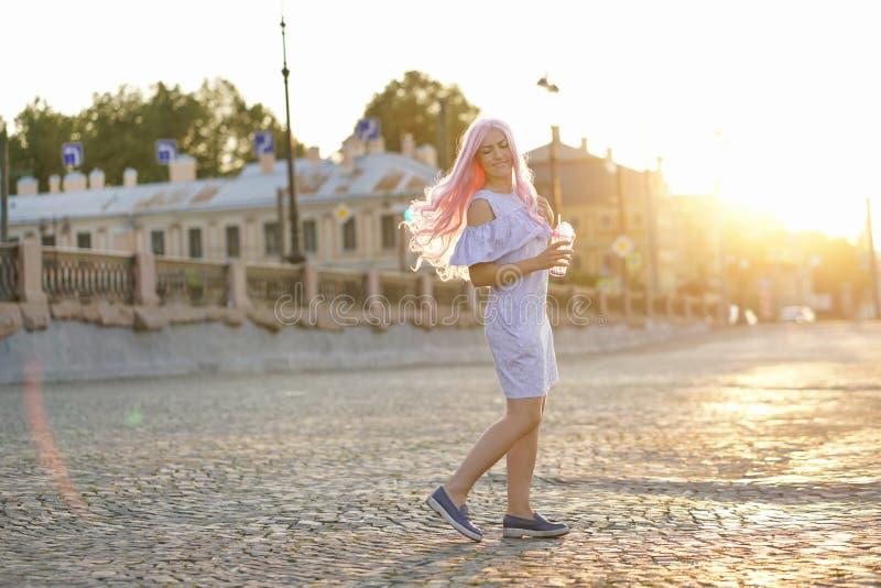 有桃红色头发的美丽的女孩在一件蓝色夏天礼服在城市附近走在与一块玻璃的黎明在她的手上 免版税库存照片