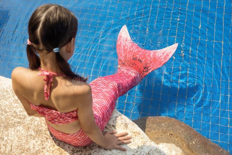 有桃红色尾巴的美人鱼女孩在游泳池边的岩石在wate投入了脚 库存照片