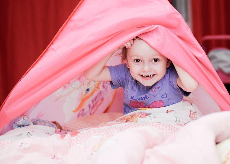 有桃红色帐篷的滑稽的小女孩 免版税库存照片