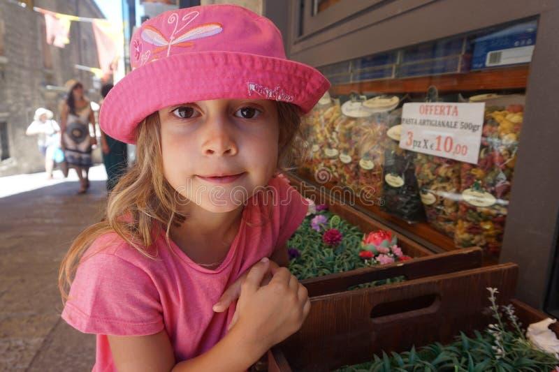 有桃红色帽子的在杂货店前面,圣马力诺女孩 免版税库存照片