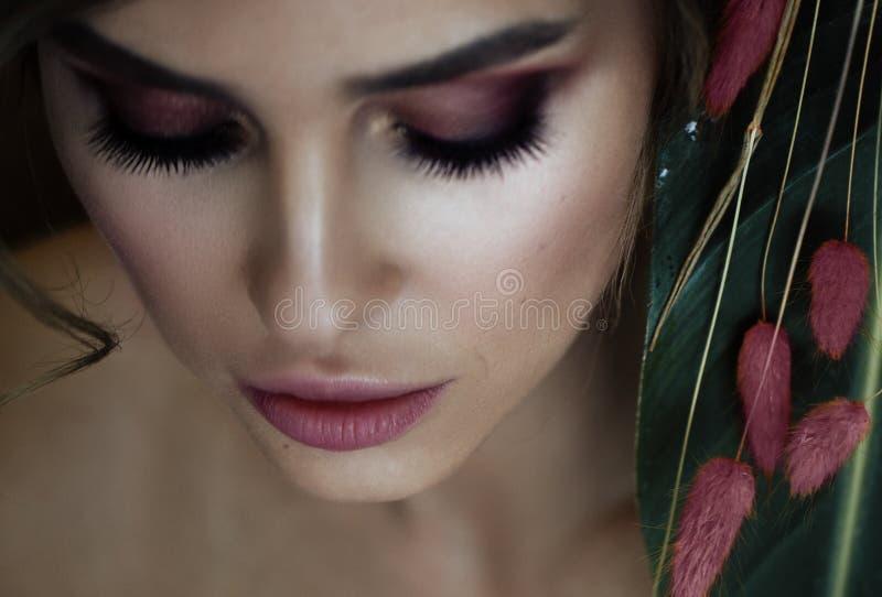 有桃红色干燥花的秀丽女孩 完善的皮肤 pe 免版税图库摄影