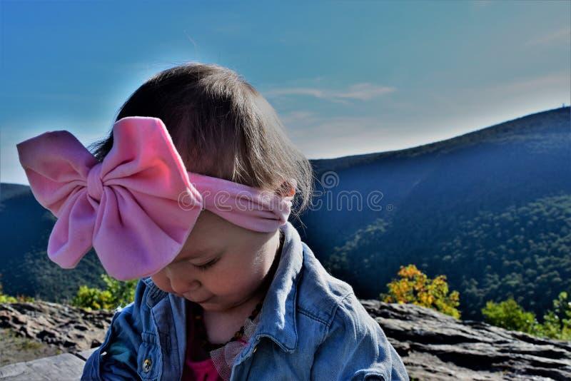 有桃红色弓的女婴在山 免版税库存照片