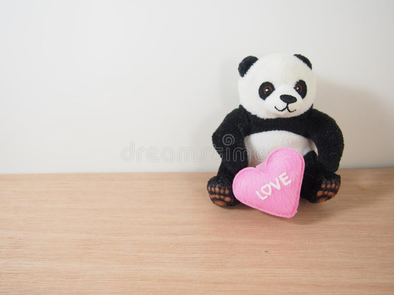 有桃红色心脏形状的软的熊猫玩偶,坠入爱河 免版税库存图片