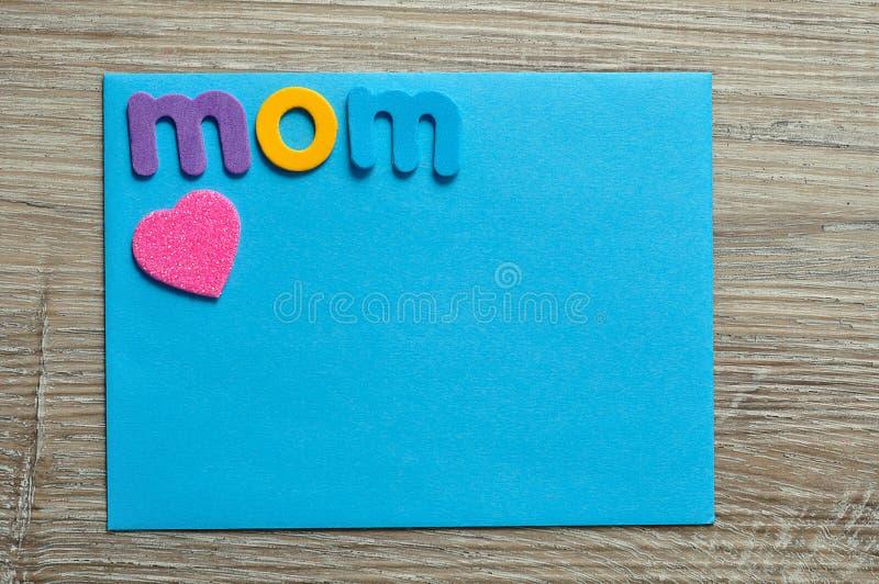 有桃红色心脏的词妈妈在一组悲伤的音符 免版税库存照片