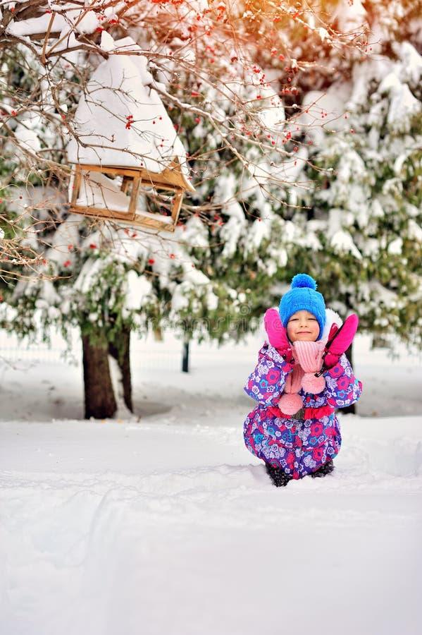 有桃红色手套的小愉快的女孩在雪森林里 免版税库存照片