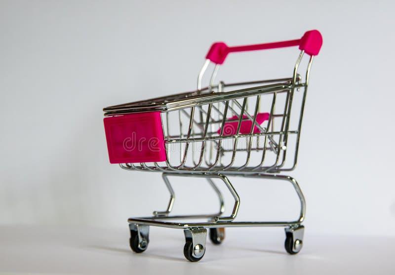 有桃红色把柄的小推车在白色背景 最逗人喜爱的装饰 今天购物概念 库存图片