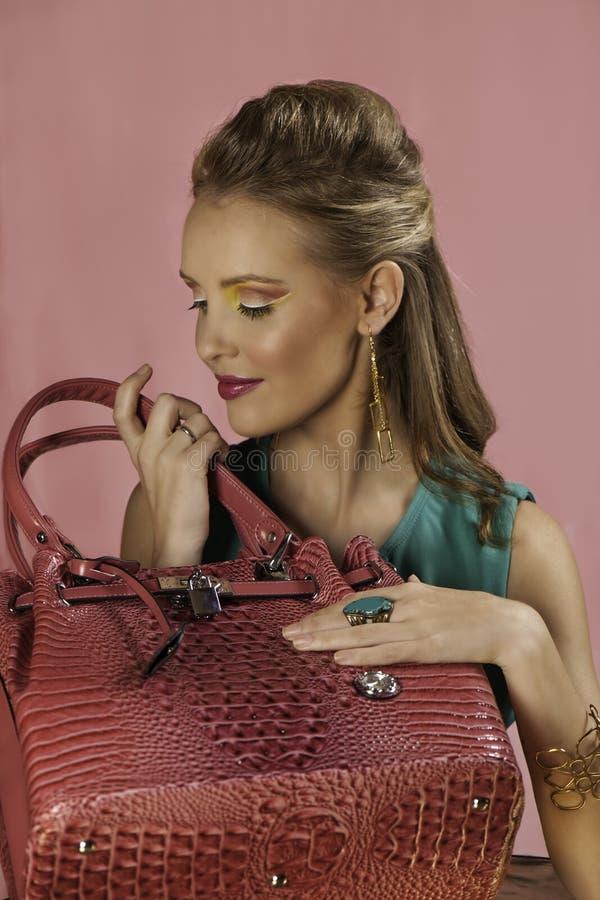 有桃红色提包的美丽的白肤金发的妇女 免版税库存照片