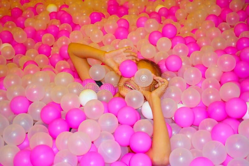 有桃红色明亮的塑料球的美丽的快乐的女孩 与多彩多姿的球的水池 免版税库存图片