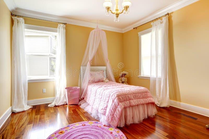 有桃红色机盖床的愉快的女孩室 免版税库存图片