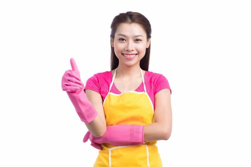 有桃红色橡胶手套showin的微笑的年轻清洁亚裔夫人 免版税库存照片